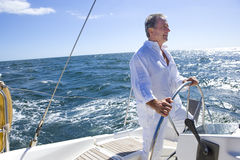 Mature man standing at helm of yacht out at sea, steering, smiling, side view (tilt) Royalty Free Stock Photos