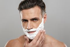 Mature man standing isolated with shaving cream on face. Photo of mature man standing isolated over grey wall background naked with shaving cream on face royalty free stock images