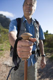 Mature man standing on mountain trail, holding hiking pole, close-up, front view stock images