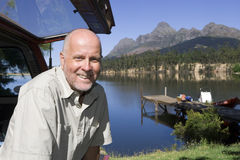Mature man standing near parked SUV, smiling, portrait, lake and jetty in background Royalty Free Stock Photos