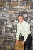 Mature man standing beside stone wall, leaning on chair, smiling, portrait Stock Image