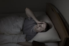 Mature man staring at ceiling during night time while in bed. Mature man, looking up at ceiling, having trouble falling asleep at night from insomnia Royalty Free Stock Photography