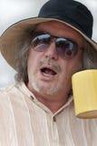 Mature man with startled expression holding mug Stock Image