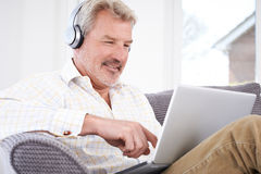 Mature Man Streams Music From Laptop To Wireless Headphones Stock Image