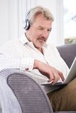 Mature Man Streams Music From Laptop To Wireless Headphones Royalty Free Stock Images