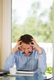 Mature man stressing out at work Stock Images