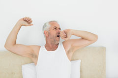 Mature man stretching arms in bed Royalty Free Stock Photos