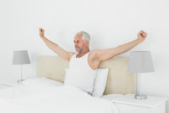 Mature man stretching his arms in bed Stock Image