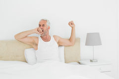 Mature man stretching his arms in bed Royalty Free Stock Photos
