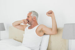 Mature man stretching his arms at home Stock Photos