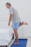 Mature man stretching his leg on an aerobic mat Royalty Free Stock Photos