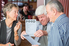 Mature Man Struggles to Read Menu Without Glasses Royalty Free Stock Image