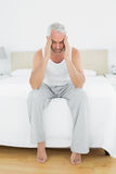 Mature man suffering from headache in bed Stock Images