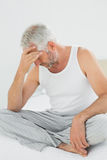 Mature man suffering from headache in bed Stock Image