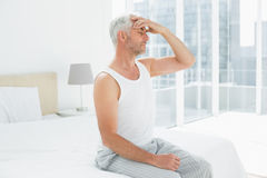 Mature man suffering from headache in bed Royalty Free Stock Image