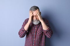 Mature man suffering from headache. On color background Stock Photo