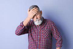 Mature man suffering from headache. On color background Stock Image
