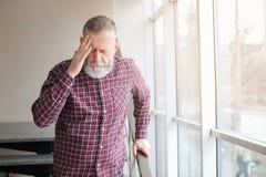 Mature man suffering from headache near window. In office Stock Photos