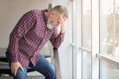 Mature man suffering from headache near window. In office Stock Images