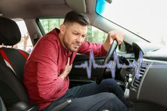 Mature man suffering from heart attack. In car royalty free stock images
