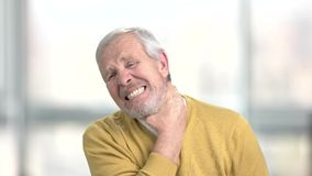 Mature man suffering from neck ache. Close up unhappy man touching his nape, blurred background. Symptoms of pinched nerve stock footage