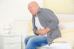 Mature man suffering from pain. At home Stock Images