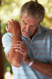 Mature Man Suffering From Painful Elbow At Home Stock Photography
