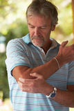 Mature Man Suffering From Painful Elbow At Home Stock Photo