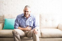 Mature man suffering from stomach ache. Old man feeling unwell with a stomach ache while sitting on a sofa at home Royalty Free Stock Photo
