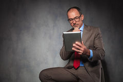 Mature man in suit thinking and using his tablet Stock Photos