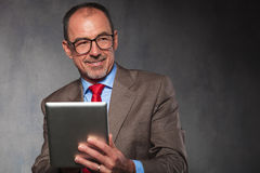 Mature man in suit wearing glasses, using his tablet Royalty Free Stock Photography