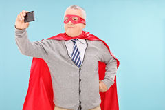 Mature man in superhero costume taking selfie Royalty Free Stock Photography