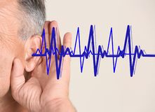 Mature man with symptom of hearing loss. On color background. Medical test royalty free stock image