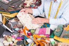 Man tailor choosing fabric. A mature man tailor choosing some fabric Royalty Free Stock Photos
