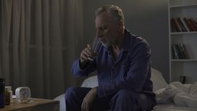 Mature man taking antidepressants and sedatives before going to bed, aging. Stock footage stock footage