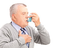 Mature man taking asthma treatment Stock Images