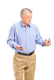 Mature man taking his medications Stock Photo