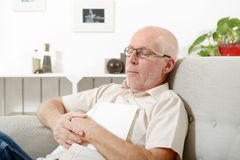 Mature man taking a nap in sofa at home Royalty Free Stock Photography