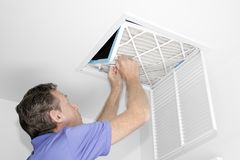 Man Removing Dirty Air Filter. Mature man taking out a dirty air filter from a home ceiling air return vent. Male removing a dirty air filter with both hands in royalty free stock image