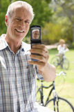 Mature man taking photograph of himself by bicycle, smiling Stock Image