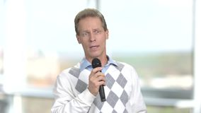 Mature man talking into microphone. Middle-aged man holding microphone and talking to audience stock video footage
