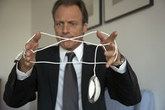 Mature man tangled in a computer mouse wire.  stock image