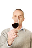 Mature man tasting red wine.  Royalty Free Stock Photo