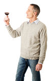 Mature man tasting red wine. Handsome mature man tasting red wine Stock Photography