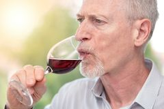 Mature man tasting red wine, light effect. Senior man tasting red wine, light effect Royalty Free Stock Photos