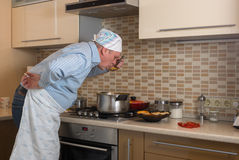 Mature man tasting Ukrainian borsch just cooked himself Stock Image