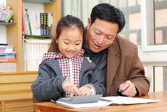 Mature man is teaching girl calculation stock photo