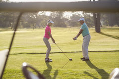 Mature man teaching woman to play golf Stock Images