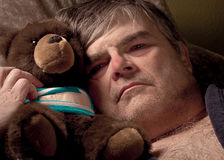 Mature man with teddy bear Stock Images