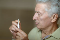 Mature man with thermometer Royalty Free Stock Photo